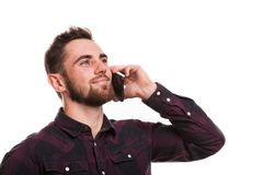 Handsome bearded man isolated on white. Close up portrait of a handsome bearded man talking on the phone, looking away happily, isolated. Attractive man smiling royalty free stock images