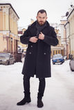 Handsome bearded man in jacket outdoors. Snow cold weather Royalty Free Stock Image