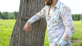 Handsome bearded man is leaning on tree in a field. Stedicam shot stock video footage