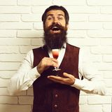 Handsome bearded man with long beard and mustache has stylish hair on happy face holding glass of alcoholic shot in. Vintage suede leather waistcoat on white stock image