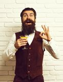 Handsome bearded man with long beard and mustache has stylish hair on smiling face holding glass of alcoholic beverage stock image