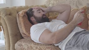 Handsome bearded man lying on the sofa checking cell phone. Guy is angry, he throws away smartphone. Receiving bad news
