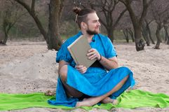 Handsome bearded man with make up, bun on head in blue kimono sitting, holding closed book stock photo