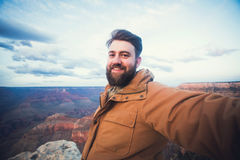 Handsome bearded man makes selfie photo on travel hiking at Grand Canyon in Arizona Stock Photos