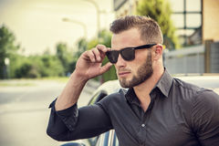 Handsome bearded man next to car in sunglasses Stock Photos