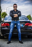 Handsome bearded man next to car in sunglasses. Portrait of young bearded man in sunglasses leaning on his new stylish polished car outdoor, with arms crossed on Royalty Free Stock Image