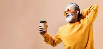 Handsome bearded man with paper cup of morning coffee stock image