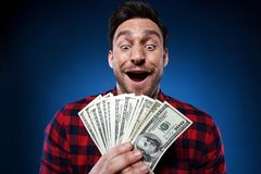 Lucky man holding 100 dollar bill money in his hand. Handsome bearded man in red shirt. Funny guy is a lucky winner, she is holding a pile of money, he is stock photos
