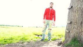 Handsome bearded man in red sweatshirt is standing near tree in a field. Stedicam shot stock footage