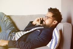 Handsome bearded man relaxing at home. Young handsome man using smartphone while resting in the sofa against empty white stock image