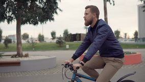 Handsome bearded man is riding a bike in summer day in city park stock video footage