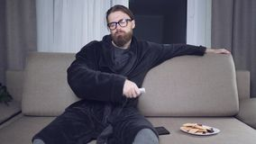 Handsome bearded man watching tv stock footage