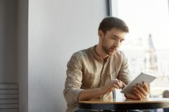 Handsome bearded man with short hair in casual clothes sitting in cafe, looking through startup project details on. Tablet. Business concept royalty free stock photography