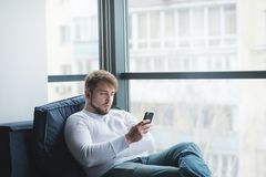 Bearded man sitting on the sofa at the window and using a mobile phone. The office worker resting on the couch stock photo