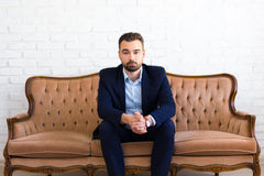 Handsome bearded man sitting on vintage sofa Royalty Free Stock Photography