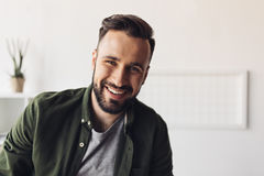 Handsome bearded man smiling at camera. Close-up portrait of handsome bearded man smiling at camera Stock Images