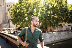 Handsome bearded man standing on bridge and looking away Stock Photo