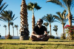 Handsome young bearded man in sunglasses sitting on the grass under palms on summer vocation luxary resort. Handsome bearded man in sunglasses sitting on the Royalty Free Stock Image