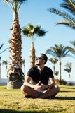 Handsome young bearded man in sunglasses sitting on the grass under palms on summer vocation luxary resort. Handsome bearded man in sunglasses sitting on the Stock Photography