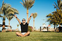 Handsome bearded man in sunglasses sitting on green grass and relax enjoy summer vocation with raised hands up happy smile on palm. Handsome bearded man in Stock Images