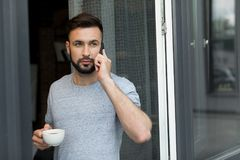 Handsome bearded man talking on smartphone while drinking coffee and looking away. At home Royalty Free Stock Image
