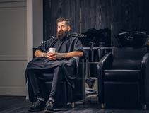 Handsome bearded man in the barbershop. Handsome bearded man with a tattoo on his arms drinks coffee before hair wash in a hairdressers salon stock images