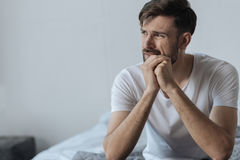Handsome bearded man thinking about his problems. Hard times. Handsome nice bearded man holding his chin and feeling unhappy while thinking about his problems Royalty Free Stock Images
