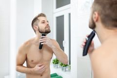 Handsome bearded man trimming his beard with a trimmer royalty free stock image