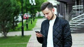 Handsome bearded man uses the phone on the street in, typing text, chatting stock footage