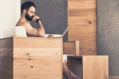 Handsome bearded man using laptop computer while resting in spa hotel. Man relaxing after hard day at spa salon. Royalty Free Stock Images