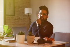 Handsome bearded man using mobile laptop computer while resting in living room at home. Man using electronic gadget. Blurred background Stock Photo