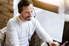 Handsome bearded man using modern devices in the cafe Stock Image