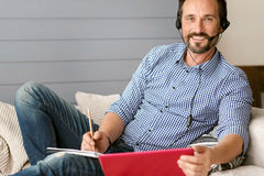 Handsome bearded man using modern devices at home Stock Image