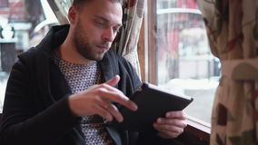 Handsome bearded man using tablet computer touchscreen in cafe. Handsome bearded man using tablet computer touchscreen sitting near a window in a cafe stock footage