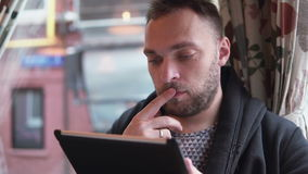 Handsome bearded man using tablet computer touchscreen in cafe stock video footage