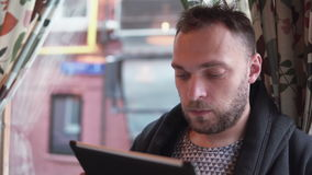 Handsome bearded man using tablet computer touchscreen in cafe stock footage
