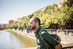Handsome bearded man walking on bridge and looking away. Summertime Royalty Free Stock Image