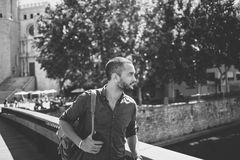 Handsome bearded man walking on bridge and looking away. Summertime Stock Photo
