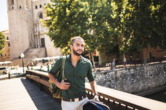 Handsome bearded man walking on bridge and looking away. Summertime Royalty Free Stock Images