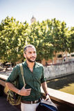 Handsome bearded man walking on bridge and looking away. Summertime Stock Photography