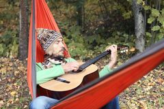 Handsome bearded man in warm hat and scarf play on guitar while Royalty Free Stock Images