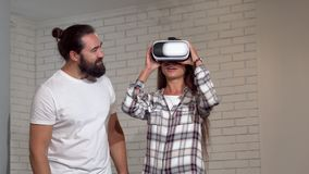 Handsome bearded man watching his girlfriend using virtual reality glasses. Beautiful woman wearing 3d vr headset with her friend standing by. Friendship stock video footage