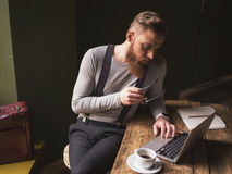Handsome bearded man is working with a laptop stock images