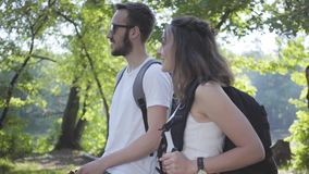 Handsome bearded man and young cute girl walking in the forest. Pair of travelers with backpacks outdoors. Leisure stock video footage