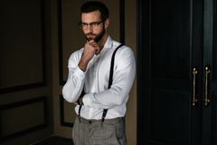 Handsome bearded pensive man in white shirt. And suspenders royalty free stock photos