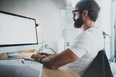 Handsome bearded professional architect wearing eye glasses working at modern loft studio-office with desktop computer Stock Image