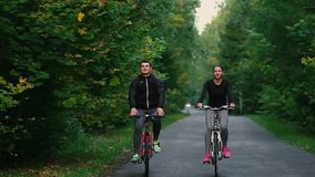 Handsome bearded professional male cyclist riding his racing bicycle in the morning together with his girlfriend, both. Wearing protective helmets and stock video footage