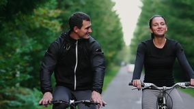 Handsome bearded professional male cyclist riding his racing bicycle in the morning together with his girlfriend, both. Wearing protective helmets and stock footage