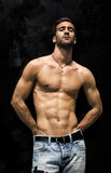 Handsome bearded shirtless young man standing against black wall Royalty Free Stock Photography