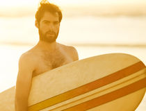Handsome bearded surfer holding a retro surfboard under his arm. Young bearded caucasian male looking at the camera while holding a retro surfboard under his arm Royalty Free Stock Photos